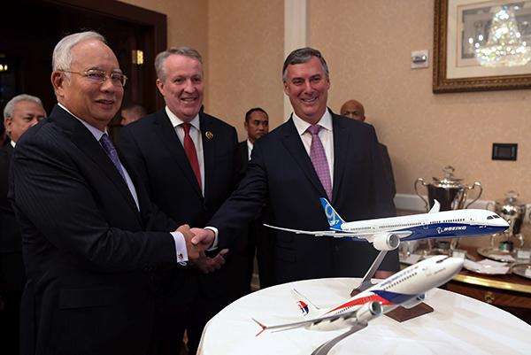 納吉(左)見證馬航與美國波音簽署諒解備忘錄后,與波音商用客機總執行長凱文握手。中為馬航總執行彼得貝柳。圖:馬新社