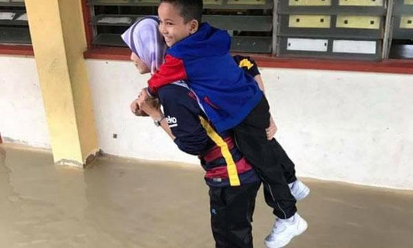 法拉諾拉希金背著其中一名學生跨過淹水的課室取物品。(圖取自《大都會日報》)