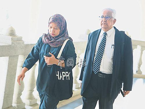 神色凝重的阿絲米拉(左)在羅納安瑟姆陪同下步入法庭。