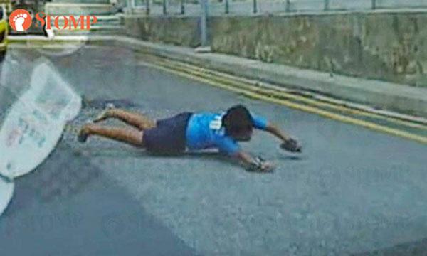 身穿藍色上衣的少年不顧安危,趴在滑板上闖出馬路。(STOMP)