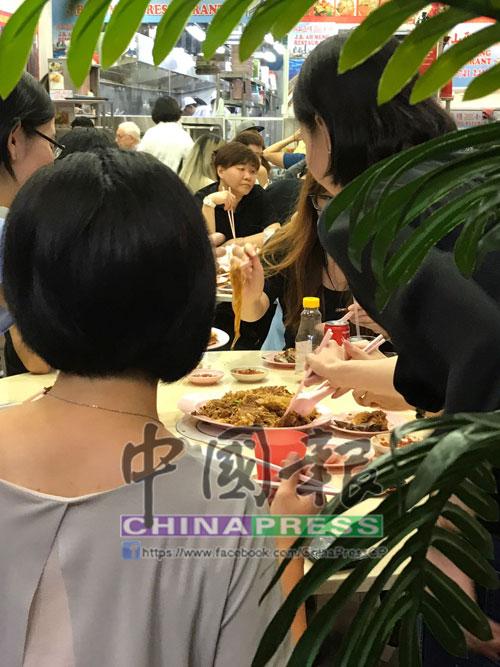 """食客正在享用亞明的招牌菜式之一""""三樓米粉""""。"""
