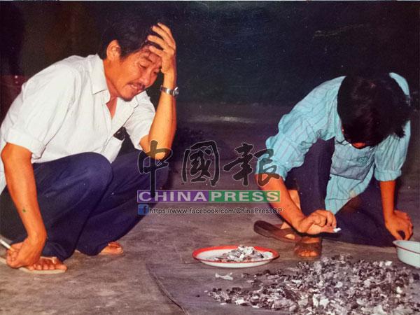 老淚縱橫的父親蹲在一旁呆望著女兒的骨灰,在一旁的哥哥也傷心的在拾著親妹妹的骨灰。