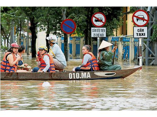 被獲救的災民週二穿上救生衣,乘坐小船經過世界文化遺產城市—會安市。(路透社)