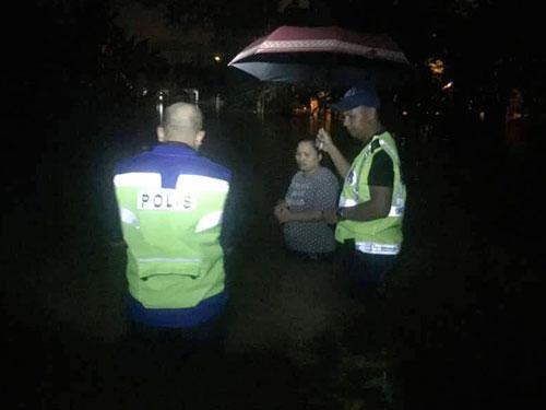 雨中現溫情,警方為一名撤離災區的居民打傘,防止她被雨水浸濕。