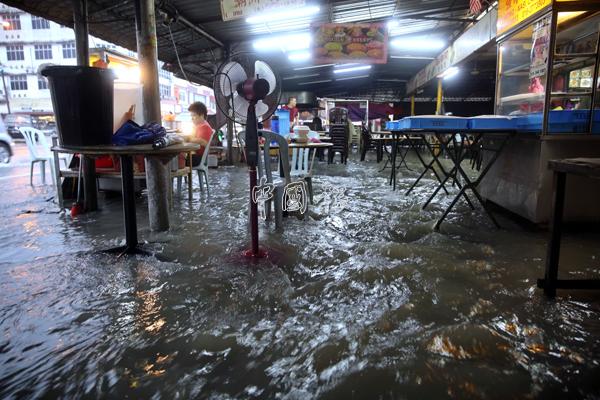 由於溝渠無法負荷大量的雨水量,導致雨水湧入小食中心內。