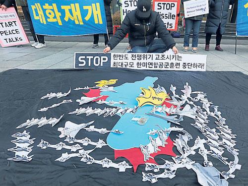 韓國示威者週一在美國駐韓國大使館前示威,抗議美韓聯合空中軍演。示威者在地上擺出韓國地圖和紙製的戰鬥機模型,表達不滿。(歐新社)