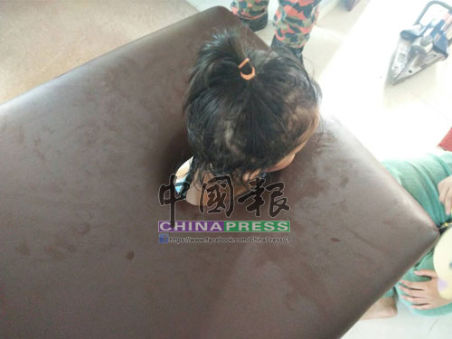 2歲巫裔女童疑貪玩,不慎把頭伸入推拿床洞,結果頭部卡著。