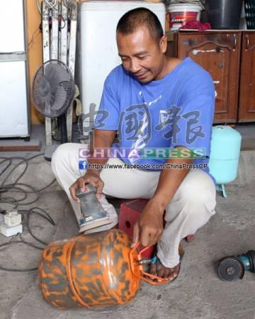 基曼里端使用機器磨除冷媒桶的外層,以便噴上漆料。