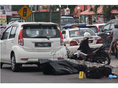 警方人員把死者遺體從溝渠抬到路面,旁為疑是死者駕來的轎車。