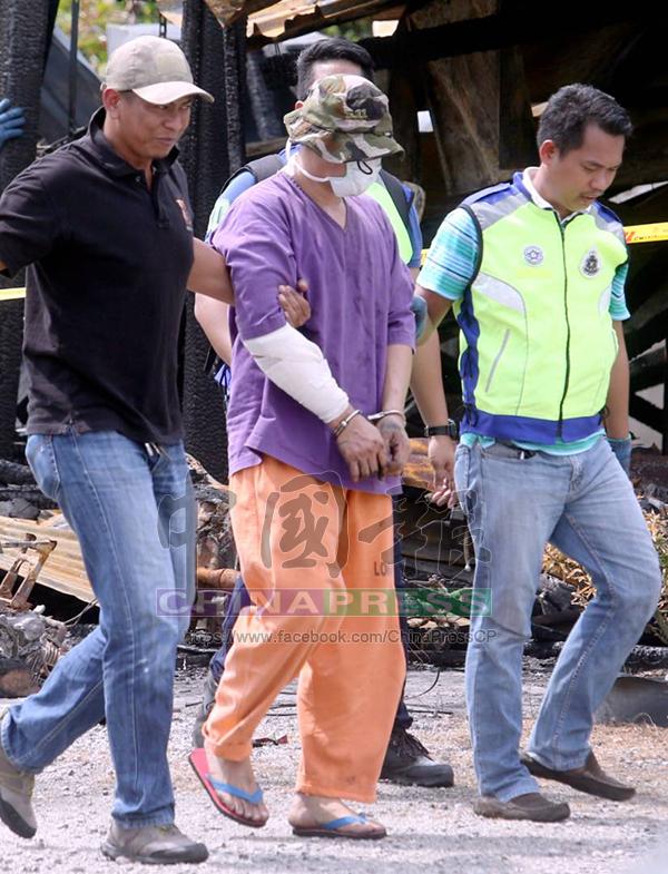 嫌犯頭戴漁夫帽、面戴口罩,手上手銬,身穿扣留所的衣物現身案發地點。