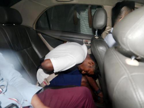 被告被警车还押进国家法院时,在车内弯下腰低着头,躲避媒体的镜头。(《海峡时报》摄影)