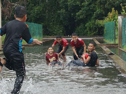 不識愁知味的孩童,在積水區嬉水作樂。