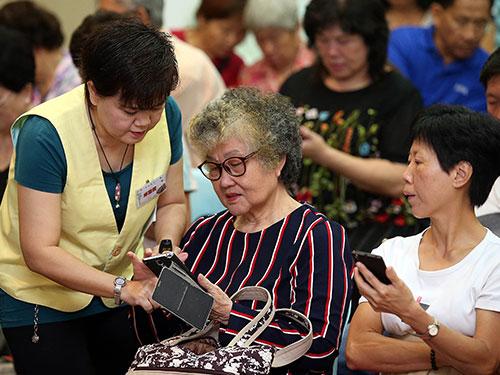 長者學員在講座會上,學習如何操作及使用智能手機。(星洲的圖)