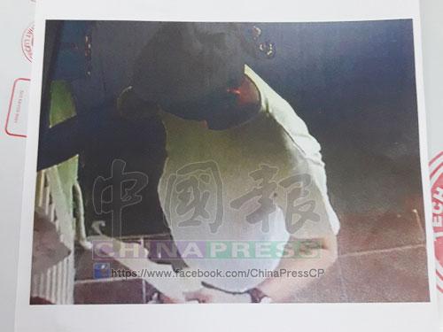 補習中心閉路電視錄影顯示一名男子正將大字報貼在門口。