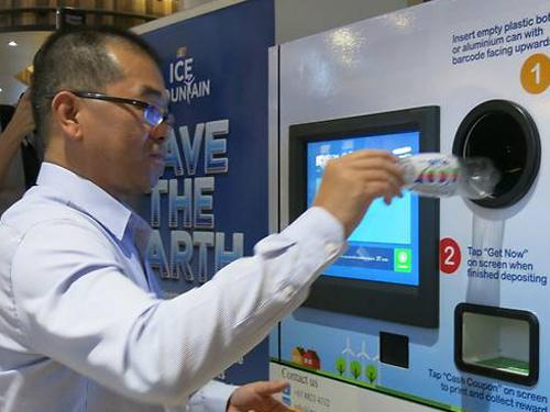 新加坡职工总会平价合作社副总执行长正在示范使用回收机。