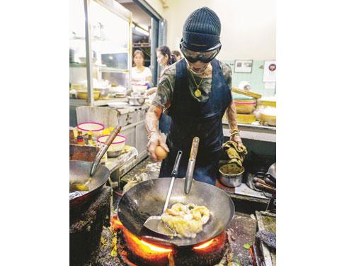 帶著黑色護目鏡的痣姐,在烹調她的成名之作——泰式蟹肉蛋卷。