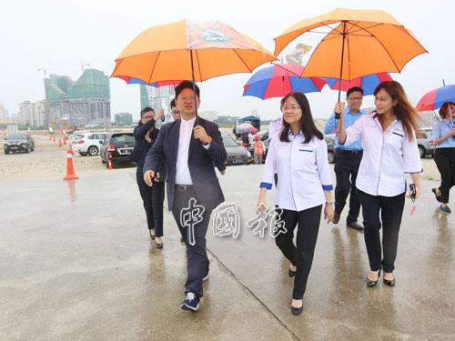 眾人撐傘前往工地,參觀皇京港計劃。