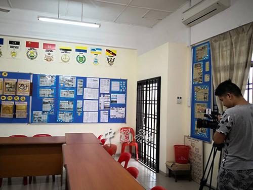 摄影师聚精会神拍摄巴莪训蒙校史馆。