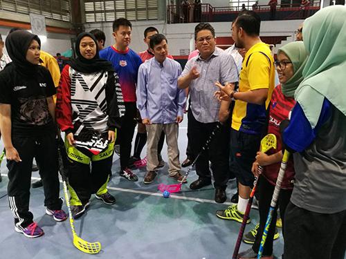 努嘉茲蘭(右4)在山甘拔士Everday Sport室內運動館體驗地板球運動。右5起是該運動館負責人戴於放及陳威勝。