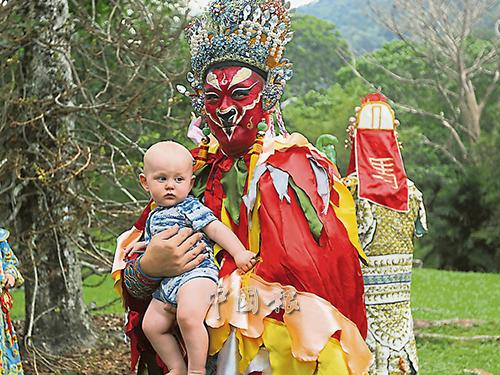 """生肖""""雞""""的洋人寶寶,在其父母了解生肖民俗后,讓寶寶與""""雞""""生肖扮演者合影紀念。"""