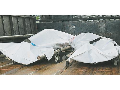 警方将两具尸体抬上卡车,送往医院太平间解剖。