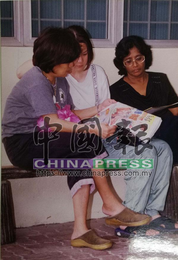 死者遺孀(中)在兩名友人的陪同下在隆市中央醫院辦理領屍手續時,閱讀《中國報》所報道有關丈夫遇害新聞。