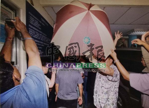 數名死者親友舉起雨傘以避免死者遺容曝光。