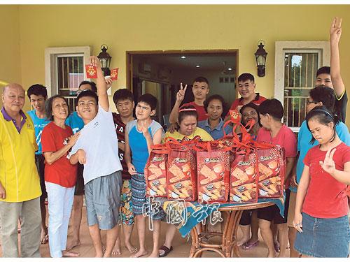 加叻喜樂涯智障人士之家眾智障男女獲分發紅包和餅乾,左起為盧振全及林素玉。