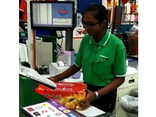 收銀員因顧客買100箱蘆柑,而掃描100次,以計算顧客所需繳付的價錢。