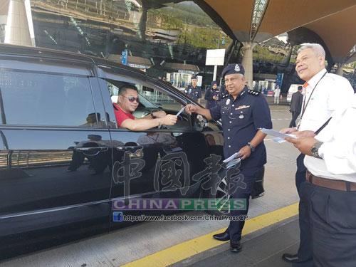 祖基菲裡(中)在吉隆坡國際機場外分發傳單給駕駛者,希望司機安全為要。右為莫哈末阿利夫