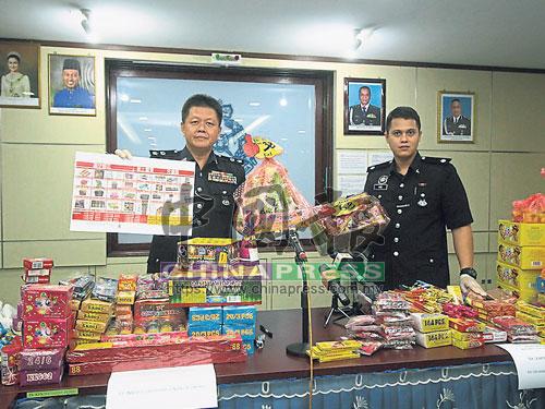 黃光順(左)展示警方起獲的32種鞭炮及煙花。