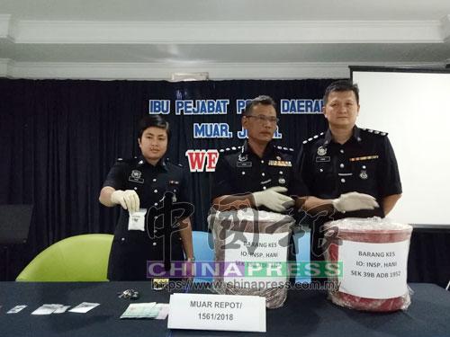 查哈魯丁(中)指警方起獲的2桶液體冰毒,總值178萬5000令吉,左起為諾哈妮及周自立。