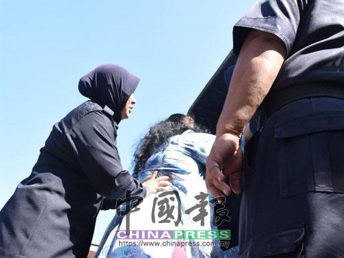 即使有女警搀扶协助,女嫌犯也很吃力的难以登上警用卡车。