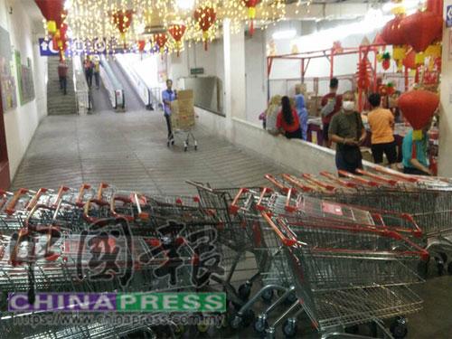 商場工作人員在通往二樓的手扶梯處,放置手推車,禁止民眾上樓。