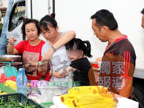 女童的父親黃志輝(右)欲帶女童(右2)一同去報案,但是女童哭著拒絕,顯然驚魂未定,最后只好讓她留在菜攤陪母親(右4)。