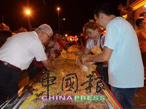 撈生之後切勿浪費食物,彭文寶(左)陪同民眾,將撈生食材放入塑料袋裡打包回家,保持愛惜食物美德。
