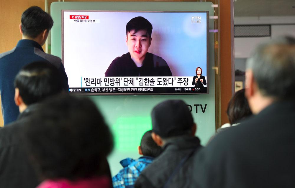 韓國首爾一處地鐵站,民眾觀看電視台轉播金正男兒子金韓松自拍的片段錄影。(法新社)