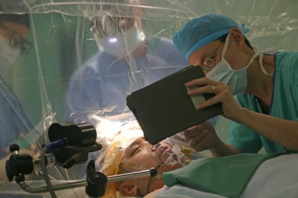醫生在胡志龍清醒的狀態下動刀切除腫瘤。(《海峽時報》)