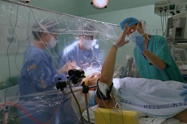 胡志龍在接受腦瘤手術時保持清醒狀態,並能按照醫生的指示抬起右臂以測量身體機能。(海峽時報)