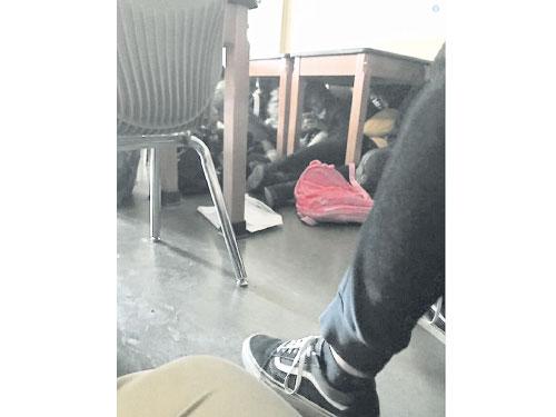 部分學生聽到槍聲后藏在書桌下的畫面。