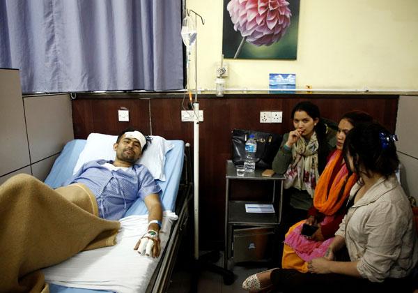 墜機生還者巴山達(27歲)在加德滿都的醫院接受治療,他的親友來醫院探望。(路透社)