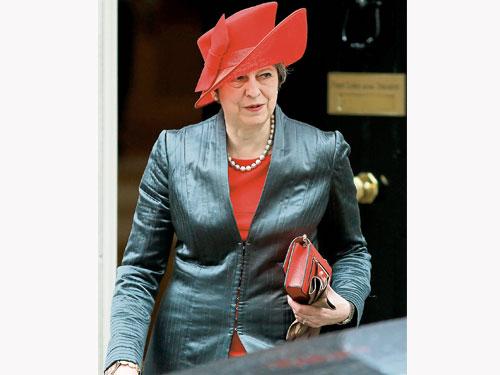 英國首相特麗莎梅周一離開首相官邸唐寧街10號,盛裝前往西敏寺出席共和聯邦日活動。(法新社)