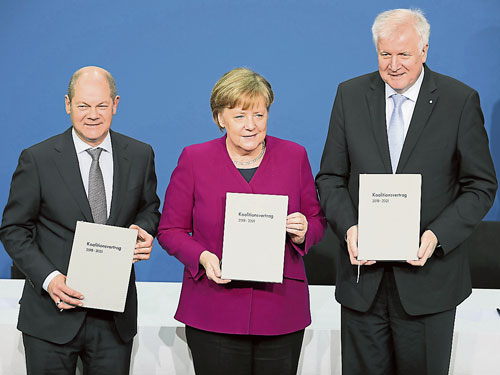 德國總理默克爾(中)、基社盟領袖澤霍費爾(右)和社民黨領袖舒爾茨,在記者會上手持達成組織聯合政府的協議文件。(歐新社)