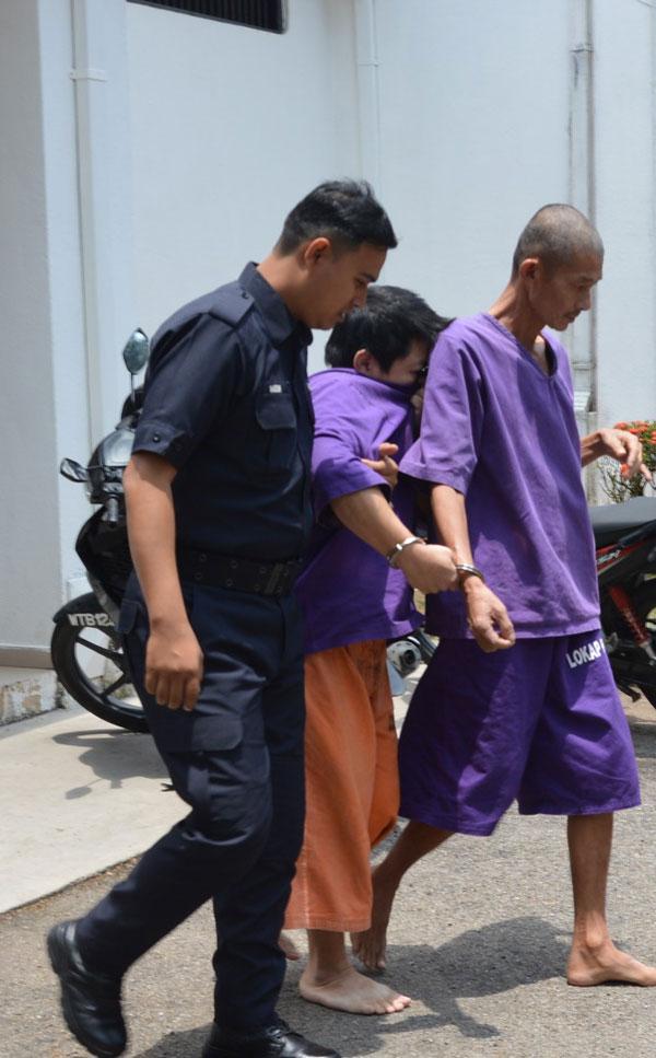 被告楊志鴻(譯音,中)被帶離法庭時,以衣服掩臉,躲開攝記鏡頭。