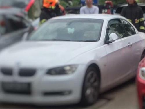 女嬰一度受困於白色寶馬轎車內,民防人員到場。(受訪者提供)