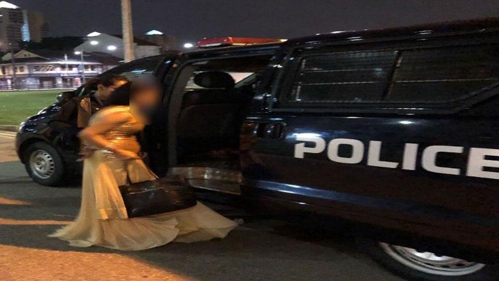 披著婚紗的女郎,被押上警車。(圖:新加坡警察部隊)