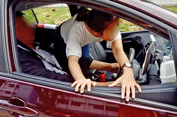 女乘客撲到駕駛座後,再從車窗爬出。(示範照)
