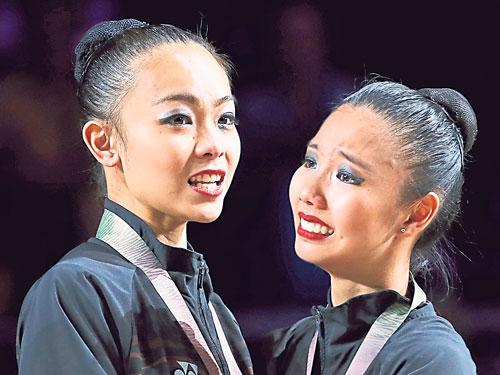 郭雪嫣(右)在頒獎上落淚,官狄雯互相安慰。2人在韻律操單項賽為大馬拿下1金2銀2銅的成績。(路透社)