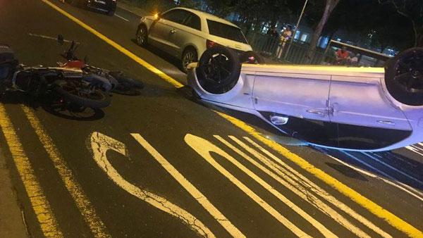 意外造成一輛摩哆和轎車四輪朝天翻覆路中央。(取自Albin Varghese面子書)