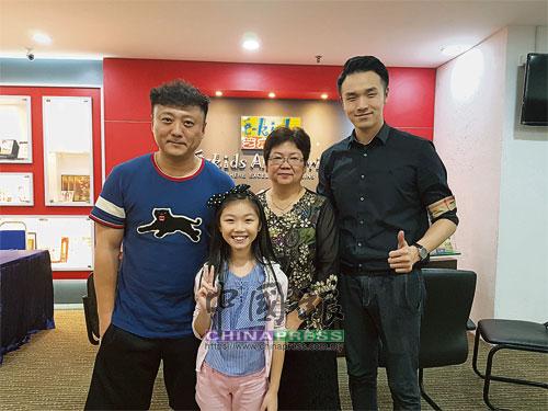 """在e-kids藝術走廊院長劉清瑩(后排中間)的邀請合作之下,李翔(左)來馬開班授課,推廣""""快樂歌唱,健康發聲""""的教學理念。"""
